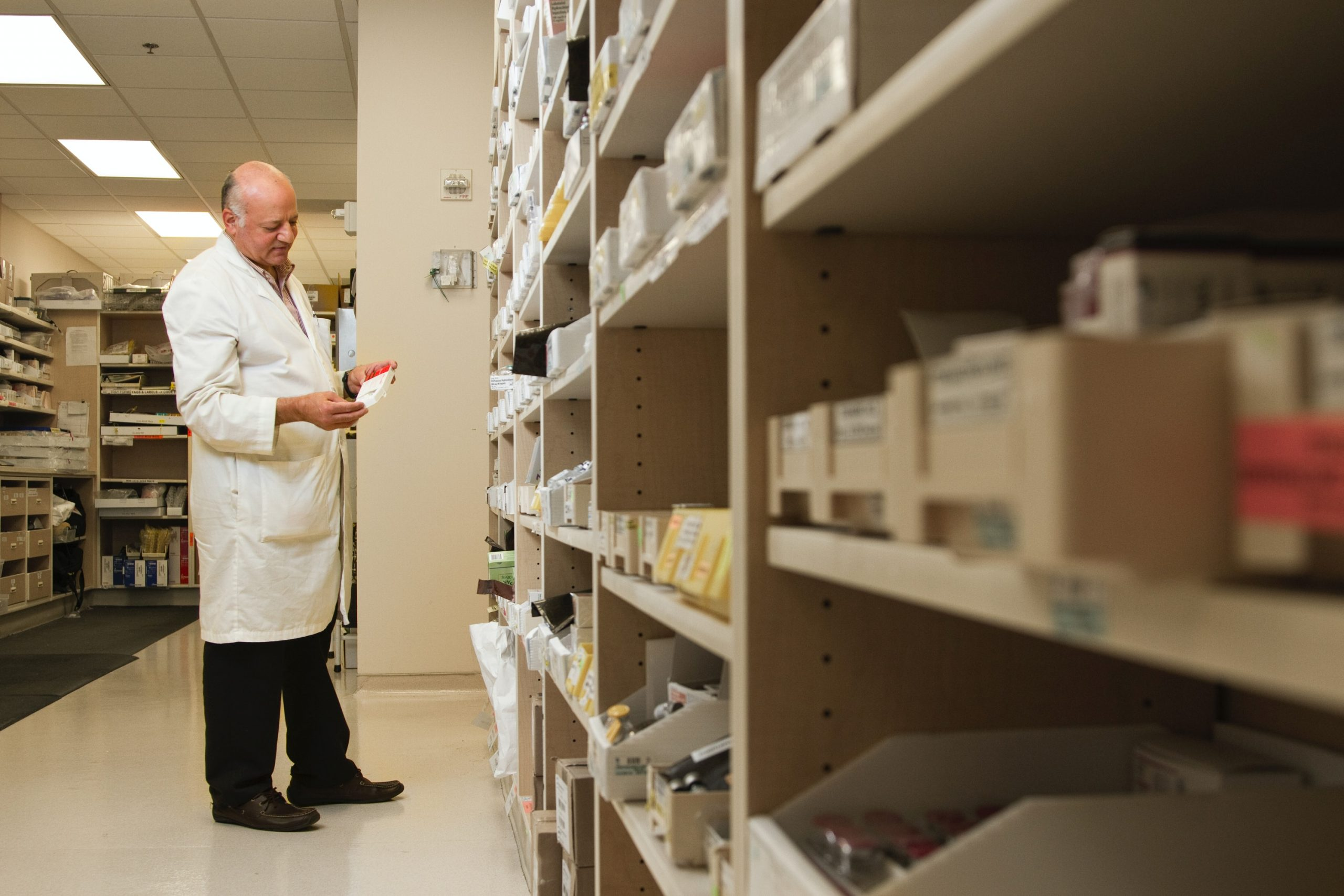 A male pharmacist is examining a drug from a the pharmacy inventory.