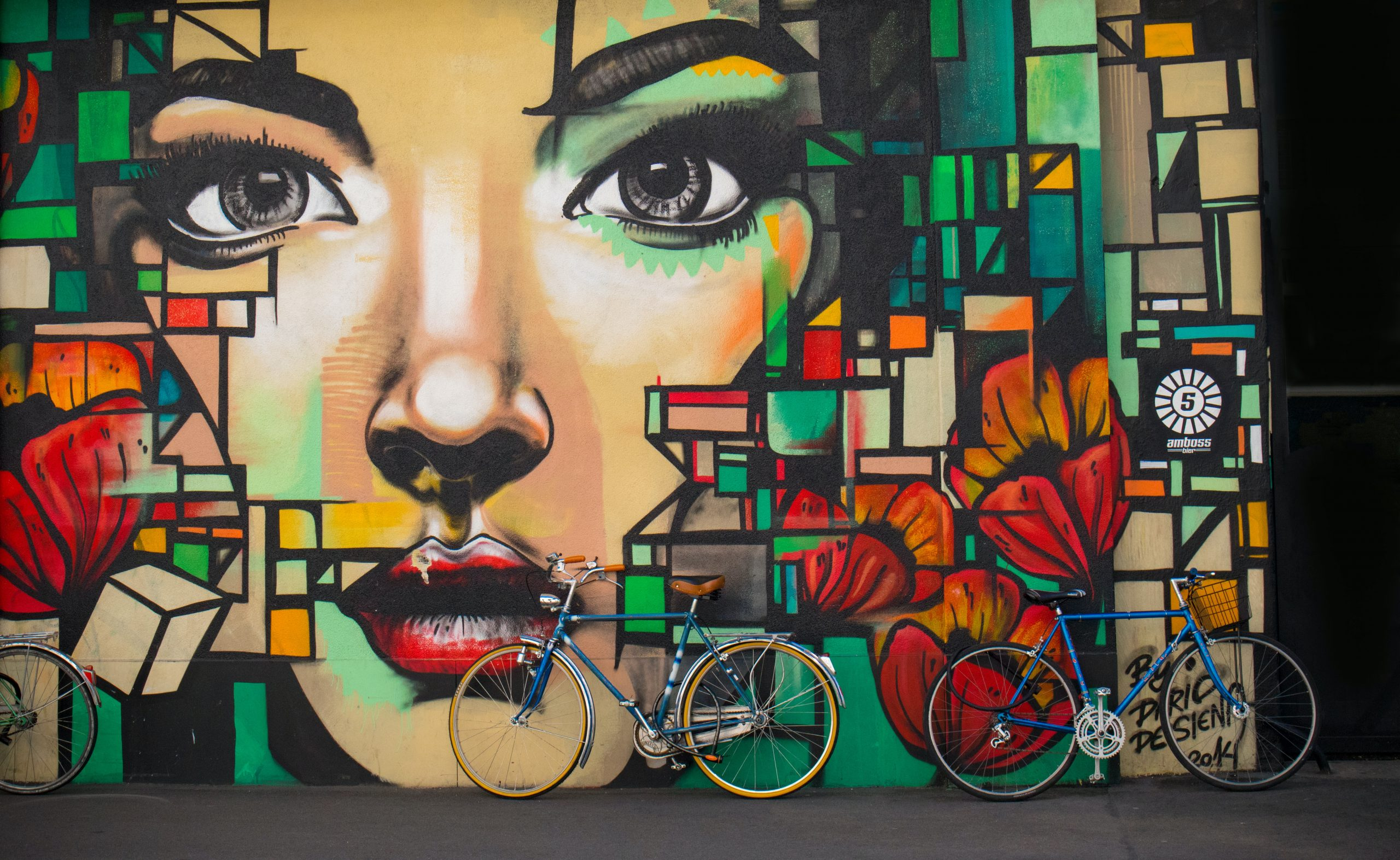 Bikes lean against wall painting