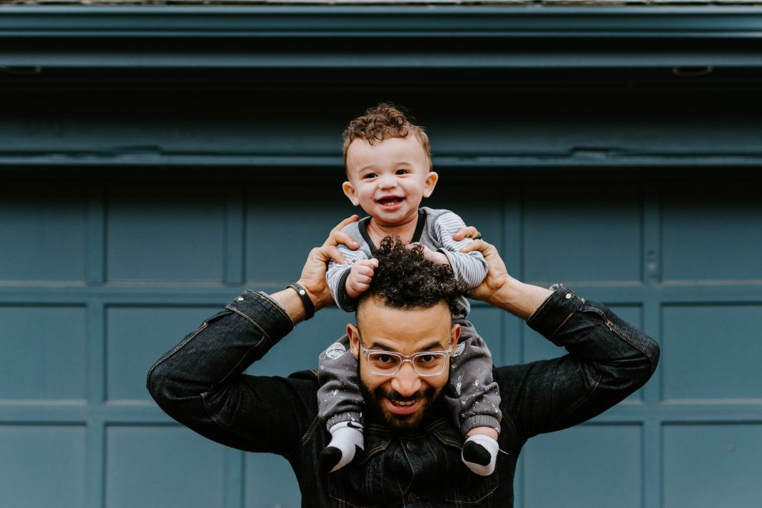Father holding his baby son on his shoulders