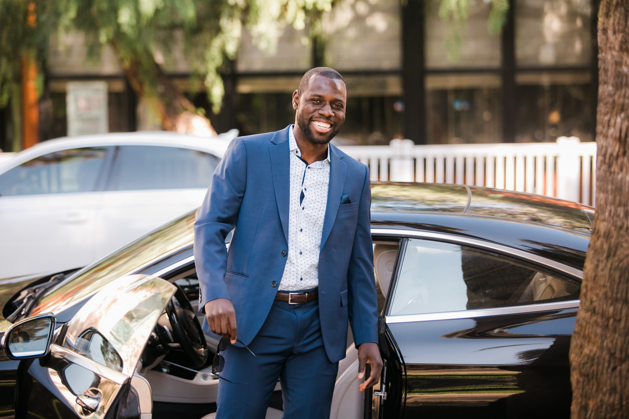 Fortune Vieyra wearing a blue business suit and smiling in front of a Mercedes