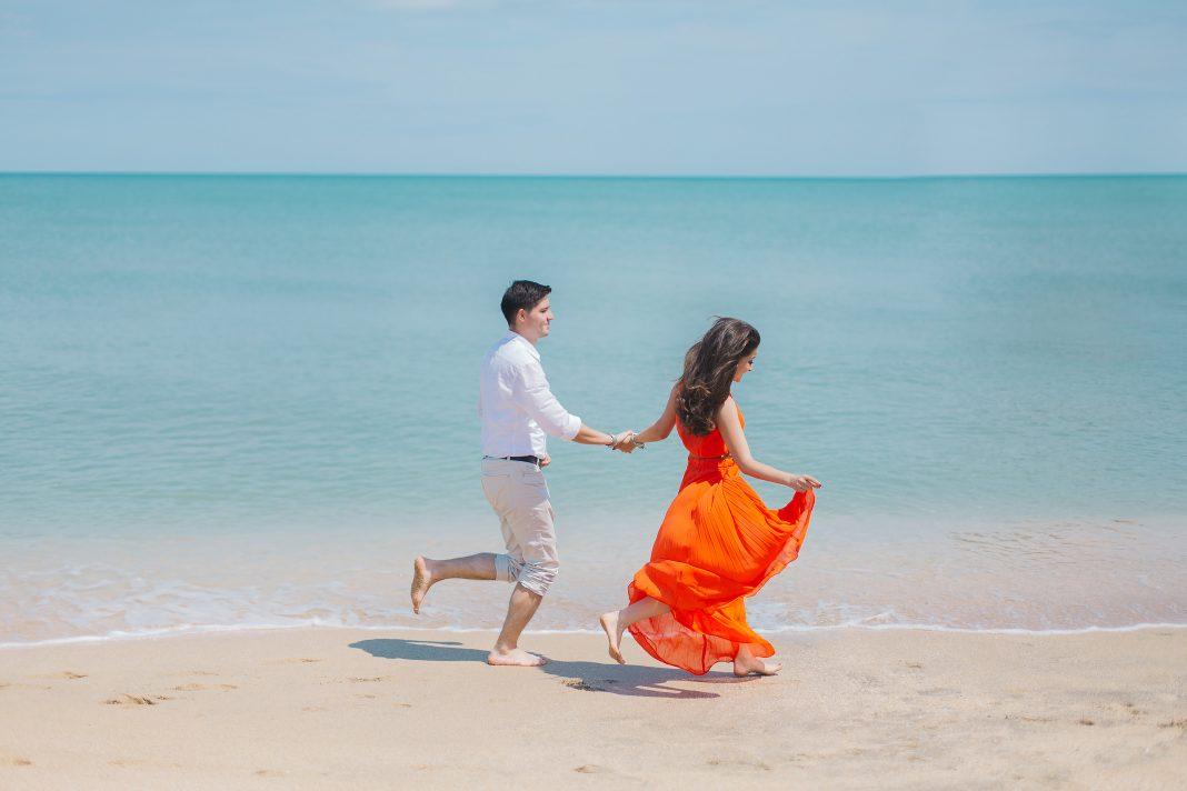 Man and woman walks beside green sea