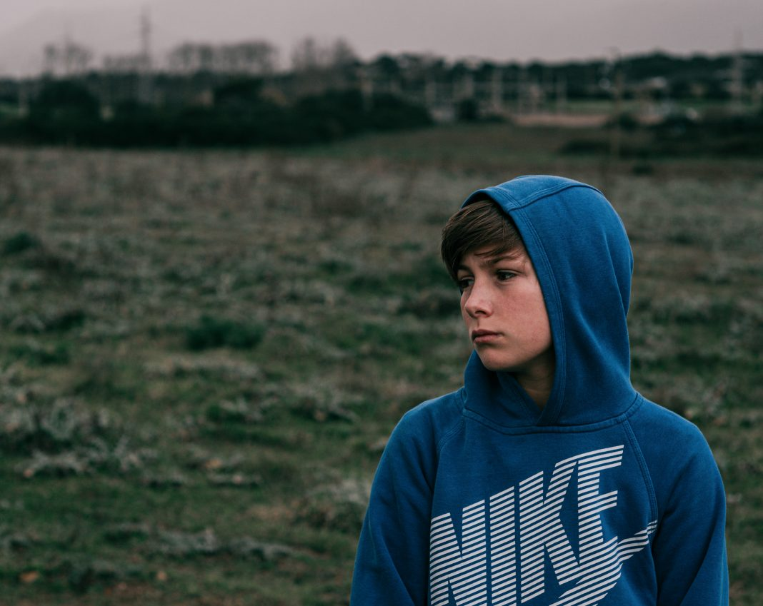 man in blue hoodie standing on green grass field during daytime