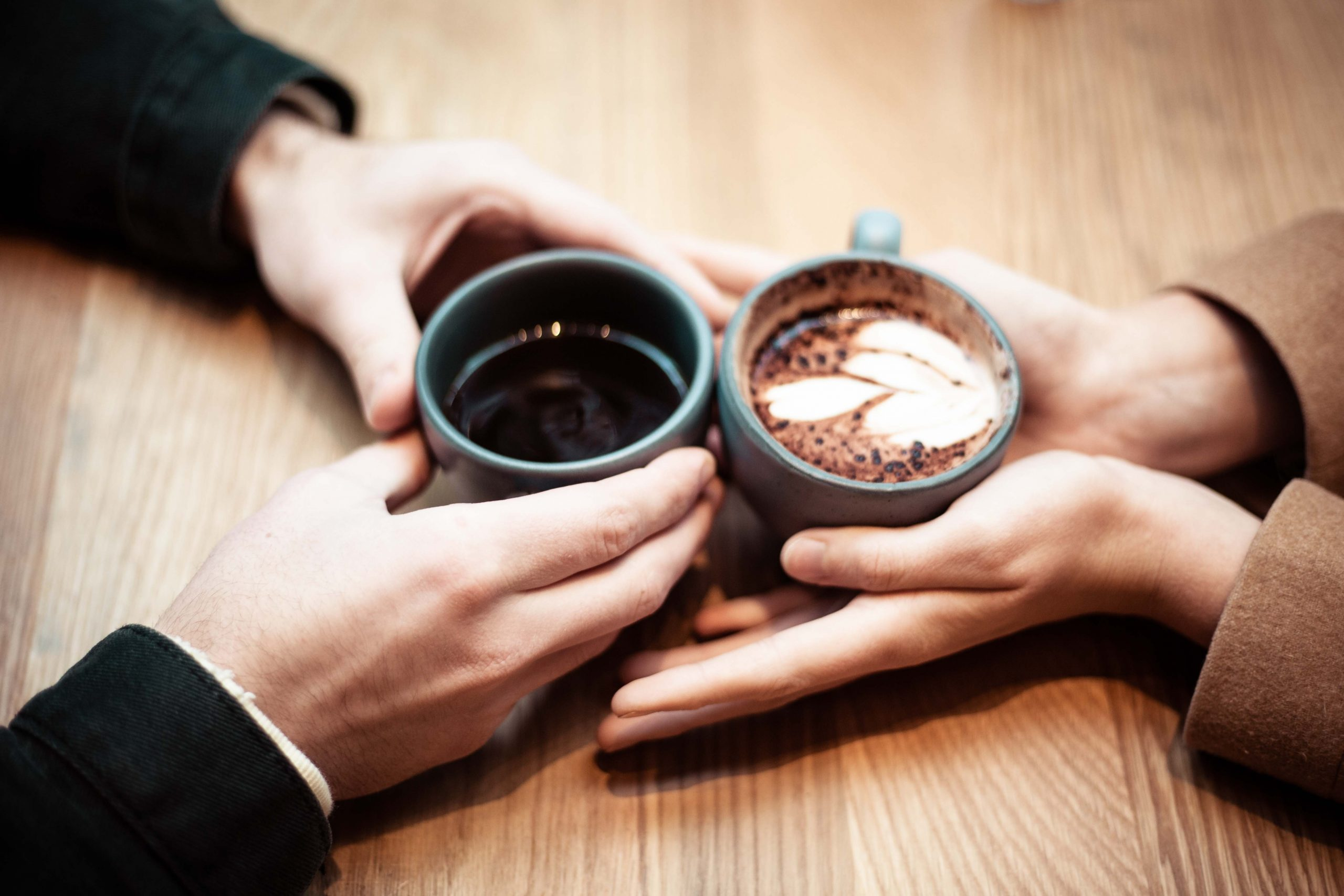 two person holding ceramic mugs with coffee