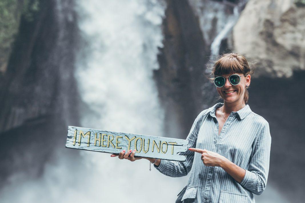 Young woman posing close to waterfall on Bali