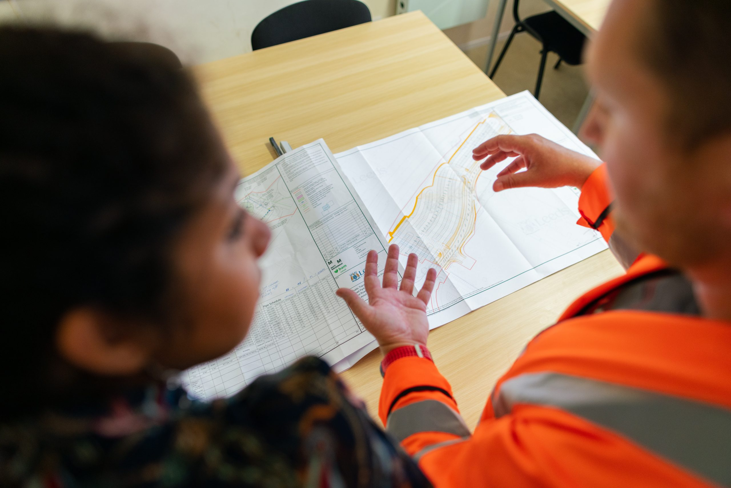 Female civil engineer discusses weir project with colleague