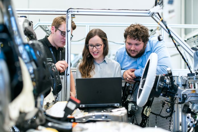 Female electronics engineer tests vehicle software with team