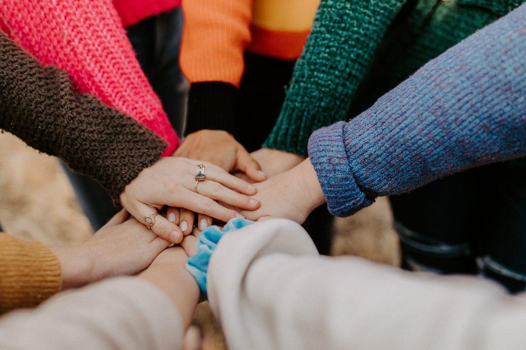 girl friends hands piled togethger