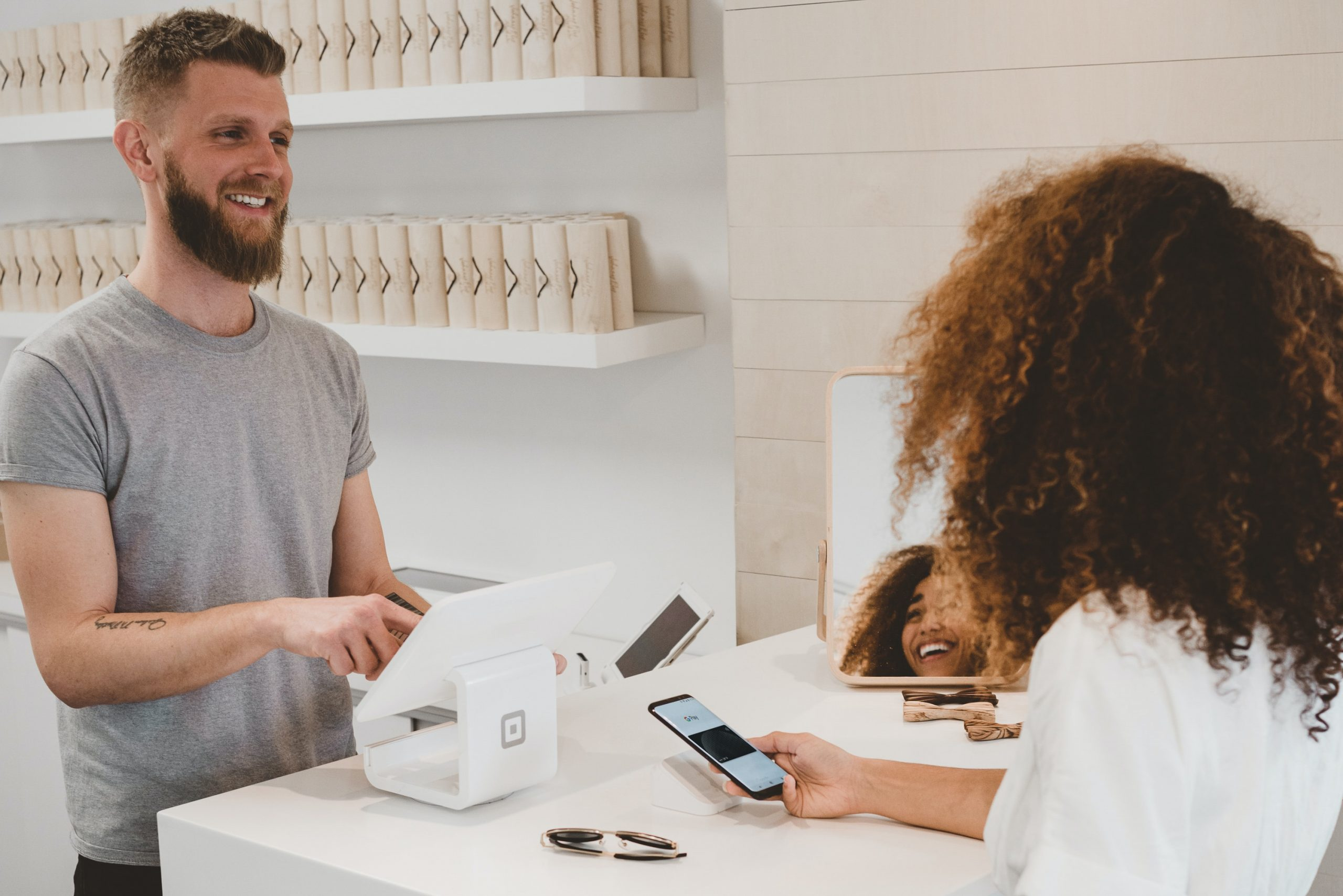 man in grey crew-neck t-shirt smiling to woman on counter