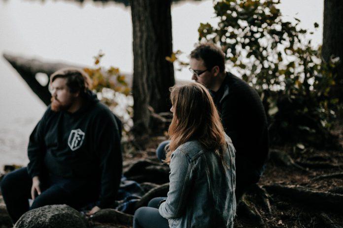 three men sitting near tree