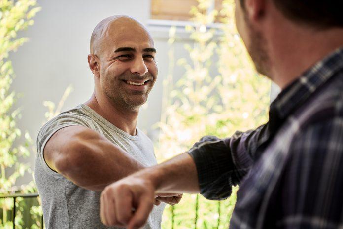 two men elbow bumping