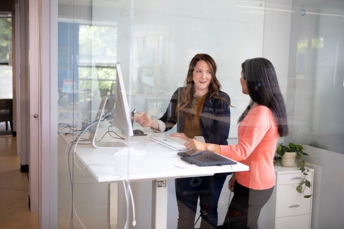 Two women at standing desk working