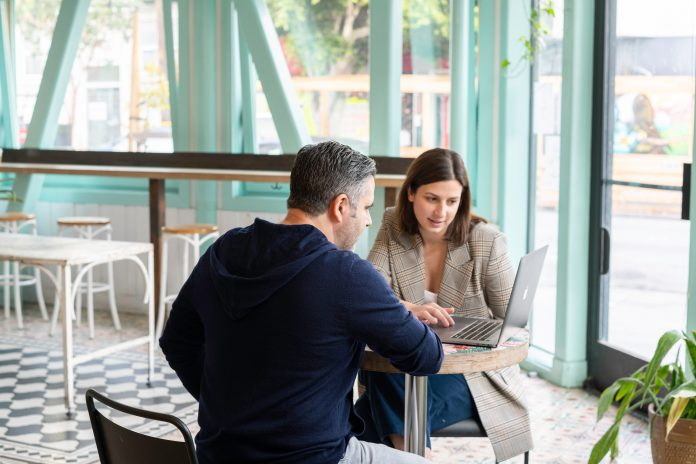 Businessman and businesswoman having a meeting in a cafe over a laptop