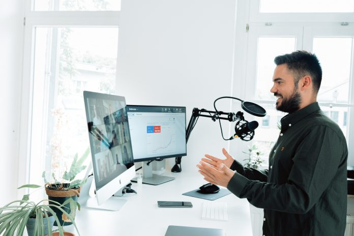 Man in a video call with two screens explaining some search engine advertising or search engine optimization techniques in a livestream or a webinar like environment.