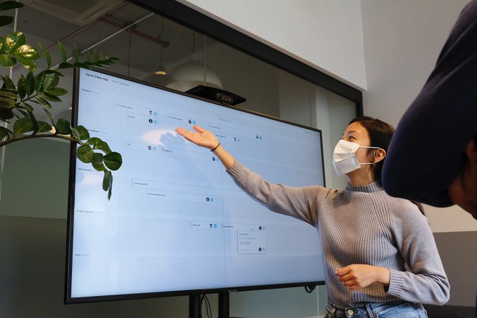 Working from WeWork in a post Coronavirus environment. Roadmap planning session with protection mask.